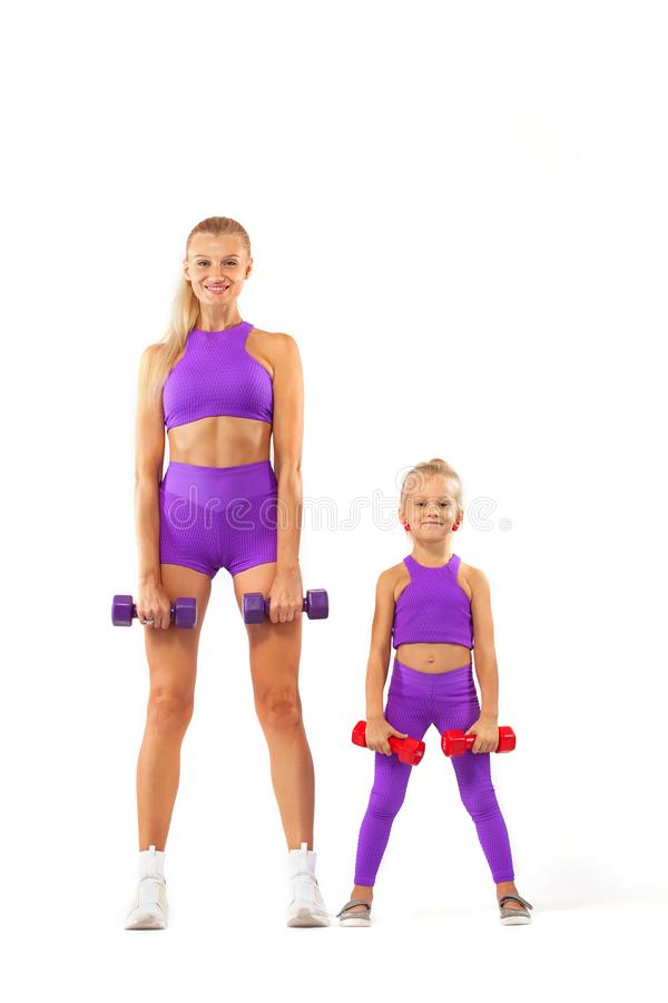 Mother trainer and kid girl doing fitness exercises with dumbbells on white background. Kid doing fitness exercises at home in her room royalty free stock image