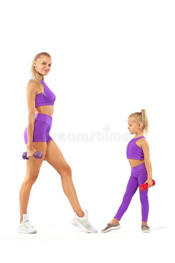 Mother trainer and kid girl doing fitness exercises with dumbbells on white background. Kid doing fitness exercises at home in her room stock images