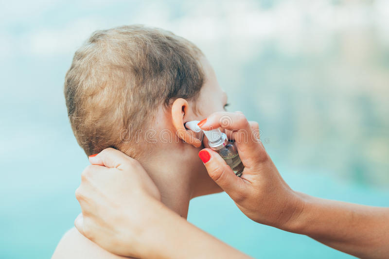 Mother treating little boy ear infection stock image