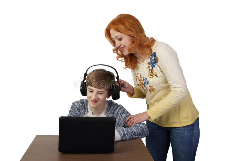Mother tries to distract son in headphones from computer stock photo
