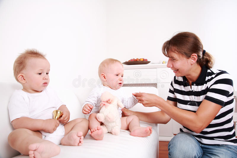 Mother with twins. Mother with two sweet babies - one looking, one crying royalty free stock image
