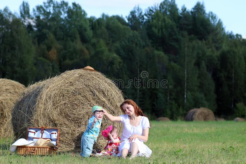 Mother with twins in field stock images