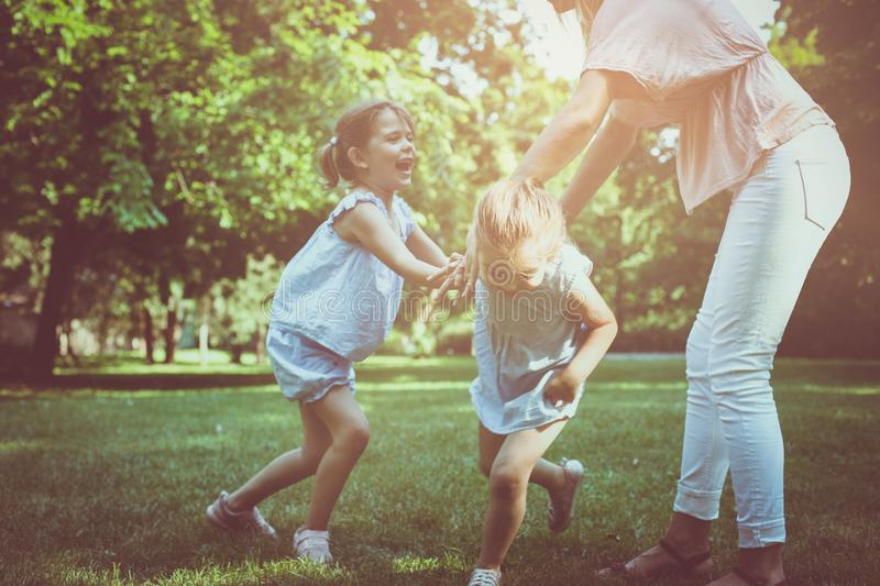 Mother with two child in meadow. Mother holding hands with girl stock photography