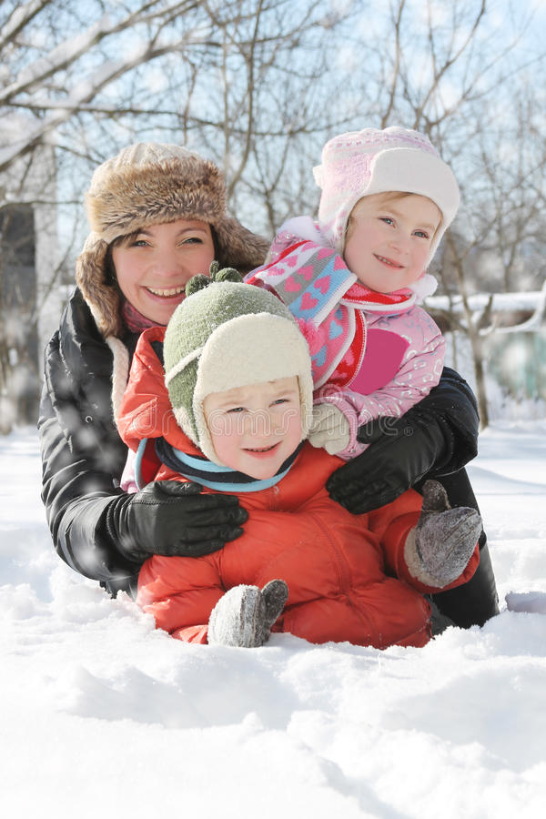 Mother with two children lying in snow