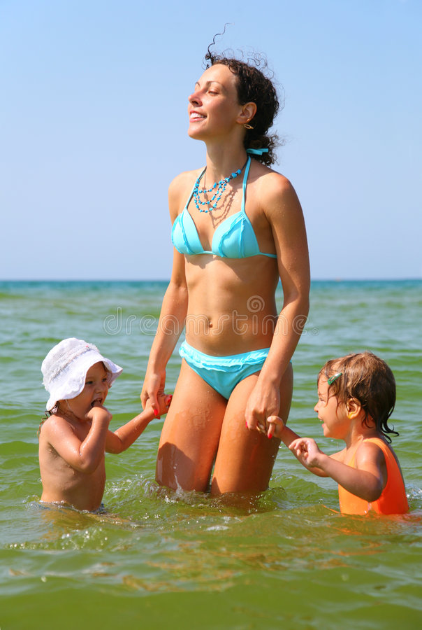 Mother and two children in sea stock photo