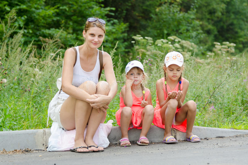Mother and two children sitting on curb of the road waiting for the bus stock photography