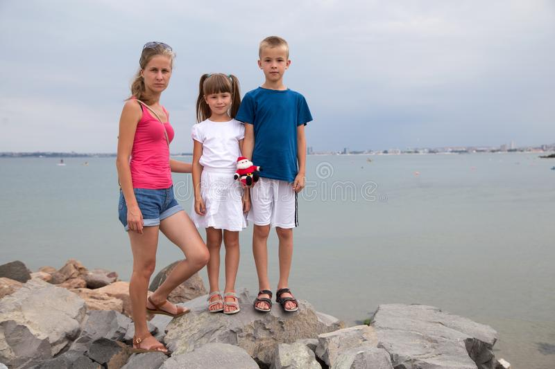 Mother and two children son and daughter standing together on big boulders on sea shore.  stock images