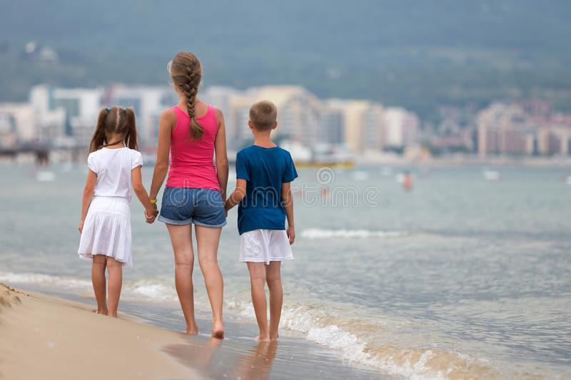 Mother and two children son and daughter walking together on sand beach in sea water in summer with bare feet in warm ocean waves royalty free stock image