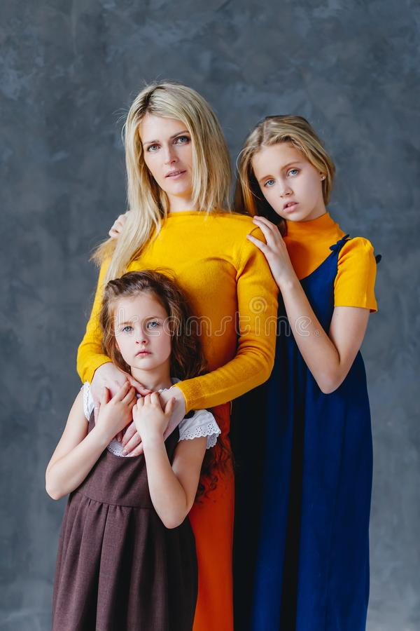 A mother with two cute daughters playing with wooden toy train. A family of four girls. A concept of big family stock photos