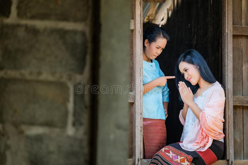 Mother and two daughters in an ancient Thai dress are scolding the daughter from wooden window royalty free stock images