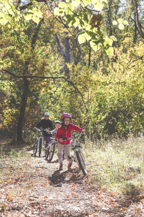 Mother and two daughters with bikes go uphill in the autumn forest royalty free stock image