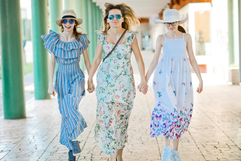 Mother and two daughters briskly walking hand in hand at colonnade. With green pillars stock photo