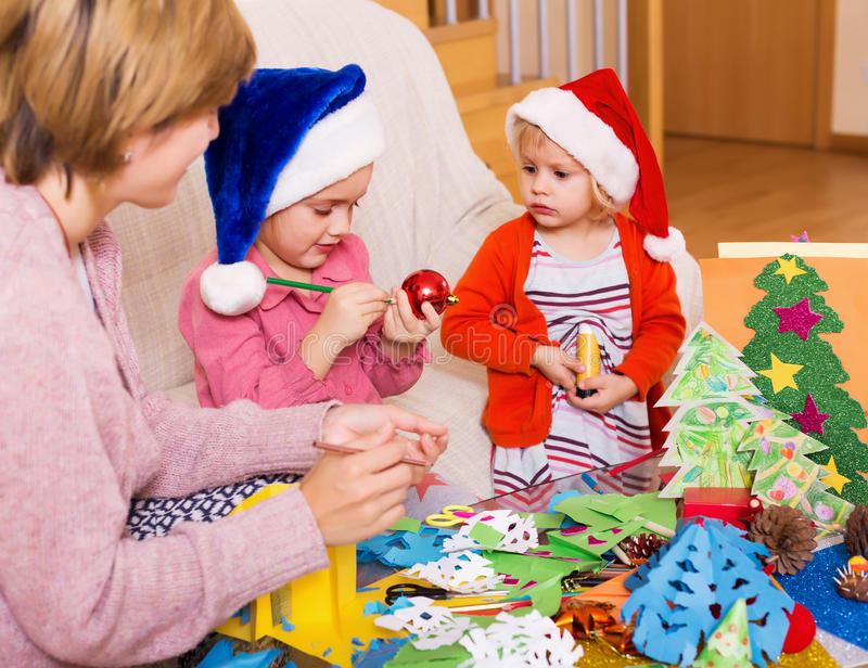 Mother with two daughters doing applique work stock photography