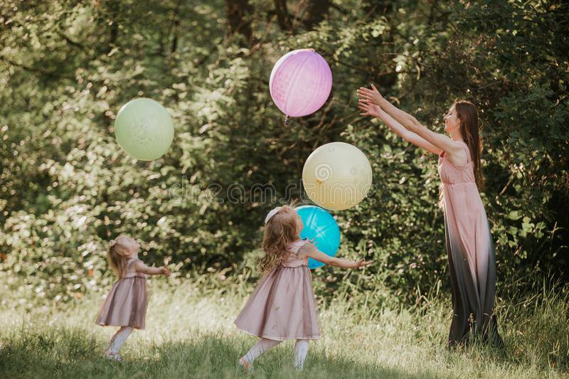 Mother and two daughters holding hands circling. Family time together. Funny time. Girls with balloons. Soft focus stock photo