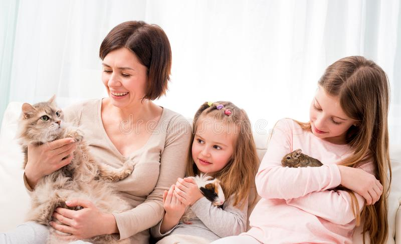 Mother and two daughters holding their favorite pets on hands. royalty free stock images