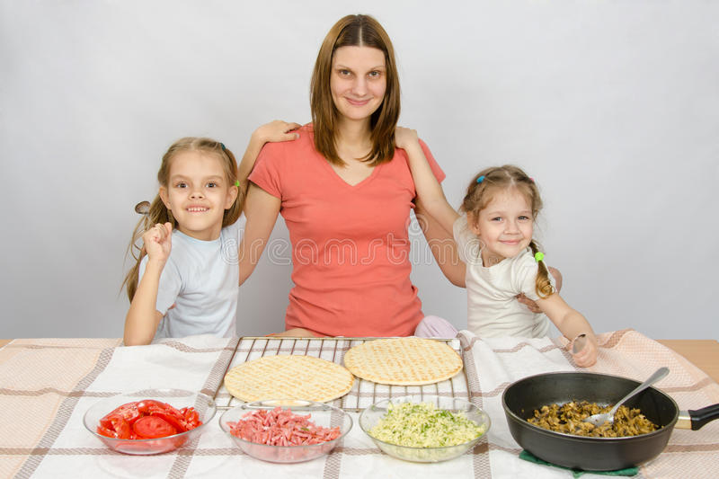 Mother with two daughters at the kitchen table are going to cook a pizza and a fun look into the frame royalty free stock photo