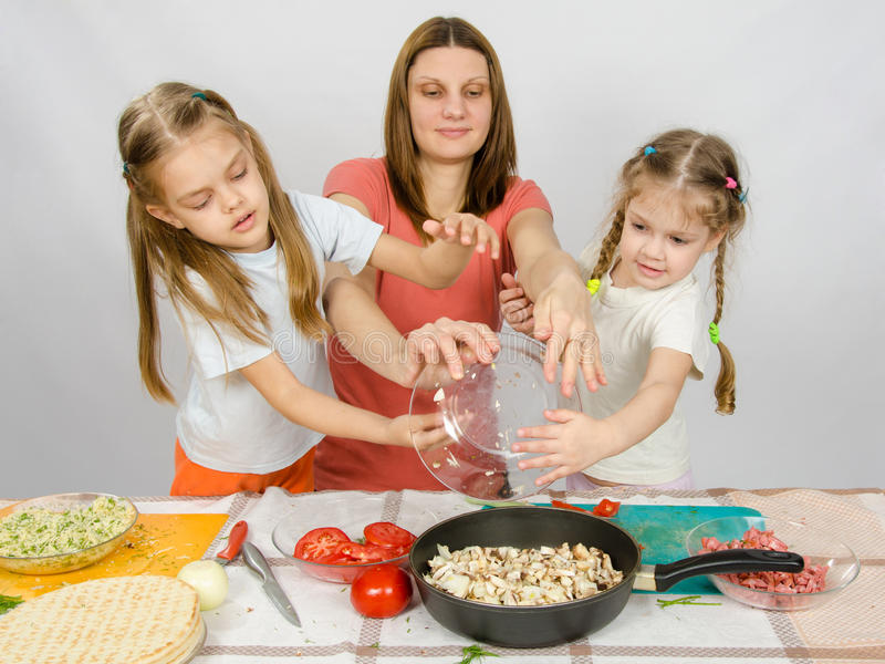 Mother with two daughters at kitchen table with a plate of mushrooms is poured into the pan royalty free stock images