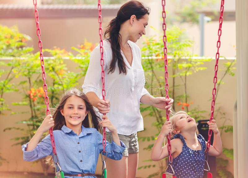 Mother with two daughters on playground. Mother with two daughters on a playground, beautiful young mom rocks her precious girls on the swing, amusement for stock photography