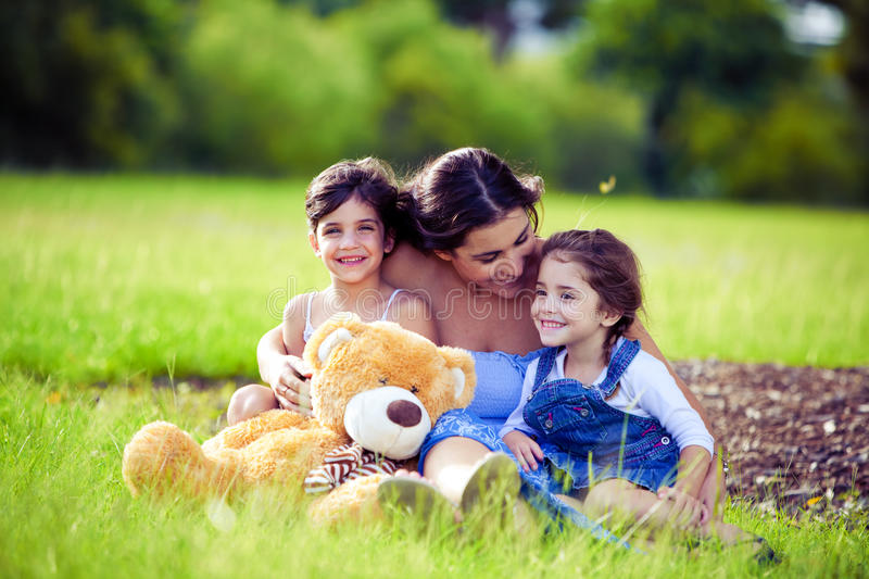 Mother And Two Daughters Playing In Grass Stock Photography