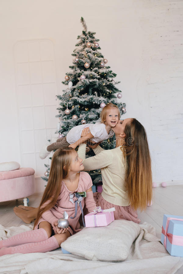 Mother and two daughters playing at at home near Christmas tree. happy family have fun for the Christmas holidays royalty free stock photography