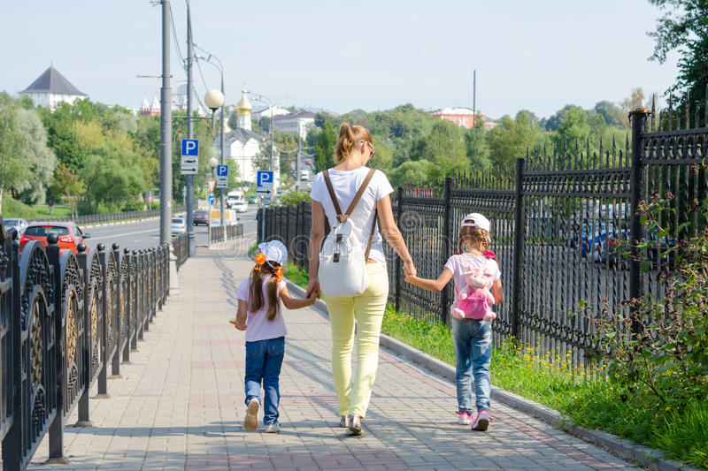 Mother and two daughters are on sidewalk along the road stock photos