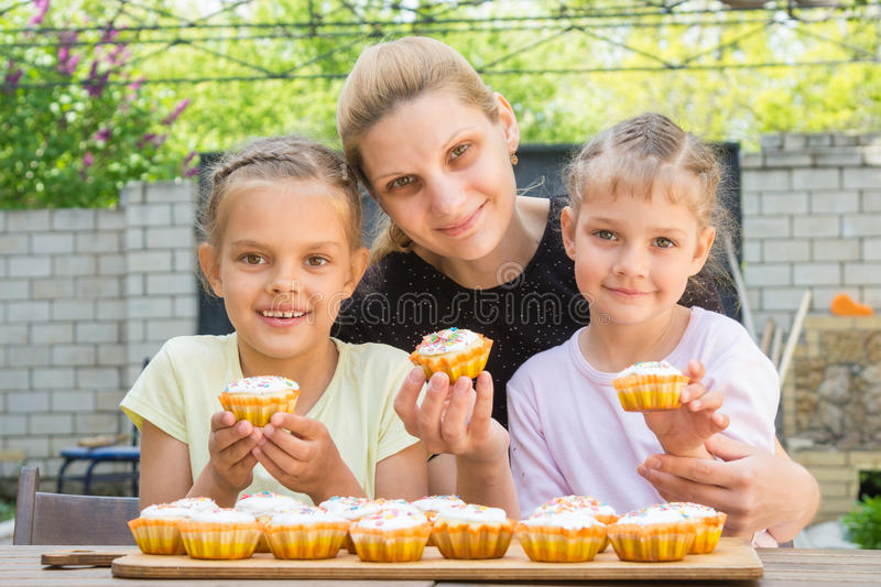 Mother and two daughters sitting at table with Easter cupcakes in his hands and looked into the frame royalty free stock photo
