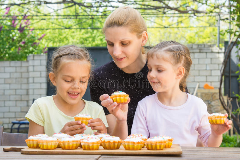Mother and two daughters sitting at table with Easter cupcakes and they are risen stock photography