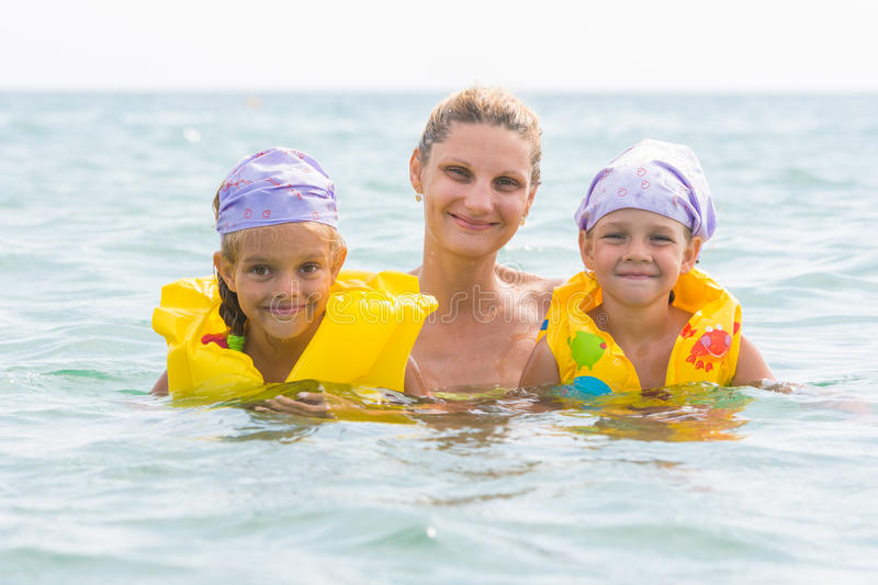 Mother and two daughters swimming in sea stock photos