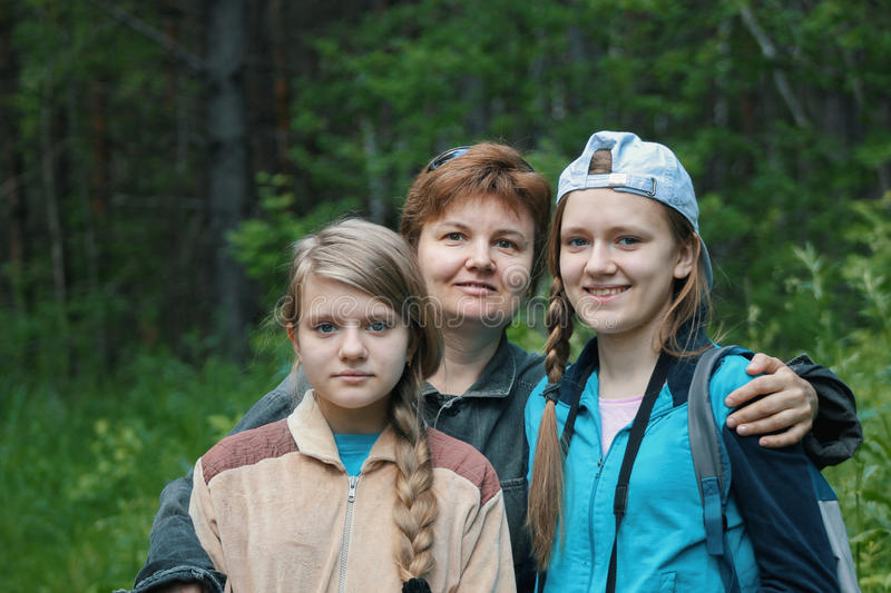 Mother and two daughters teenagers in park stock photo