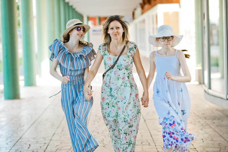 Mother and two daughters walking hand in hand at colonnade stock photos