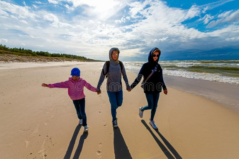 Mother with two daughters walking on the sandy seaside beach on a sunny day - a family walk by the sea royalty free stock photos