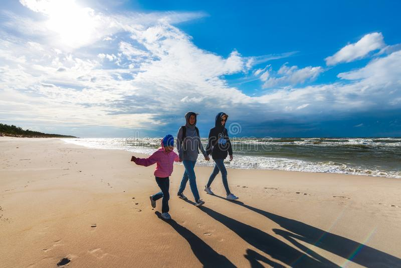 Mother with daughters walking on the seaside beach on a sunny windy day - a family walk by the sea. Mother with two daughters walking on the seaside beach on a stock images