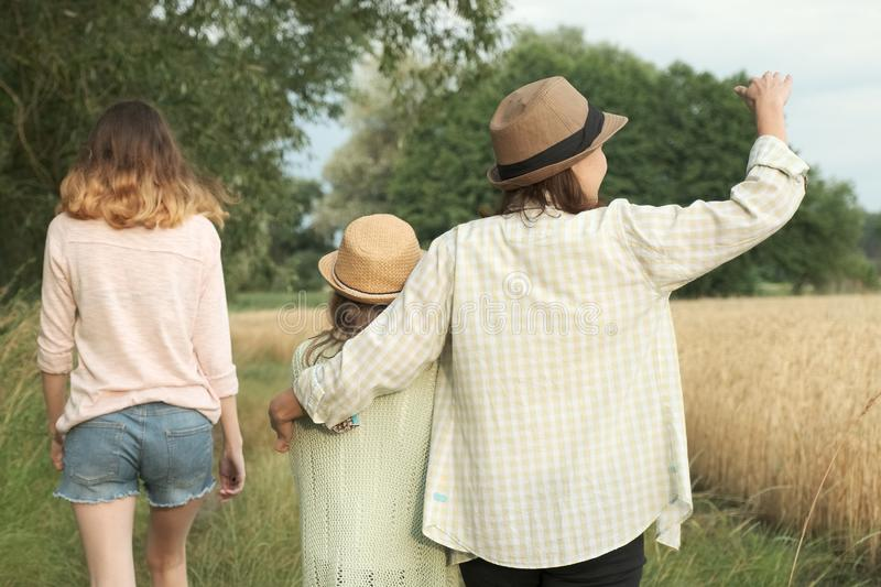 Mother and two daughters walking together along country road, back view royalty free stock image