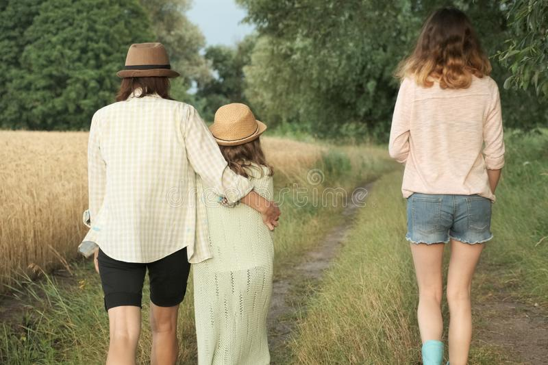 Mother and two daughters walking together along country road, back view stock images