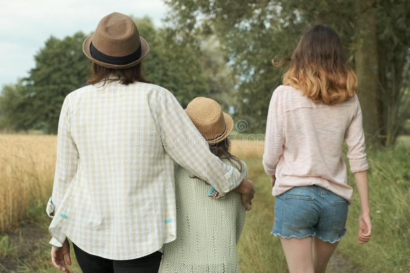 Mother and two daughters walking together along country road, back view stock photography
