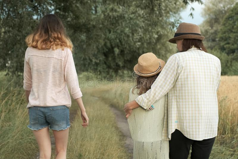 Mother and two daughters walking together along country road, back view stock photo