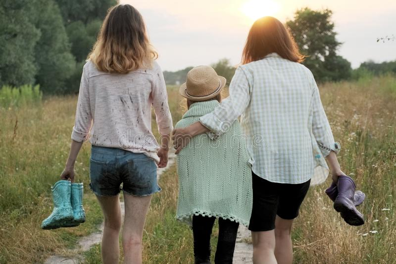 Mother and two daughters walking together along country road royalty free stock photo