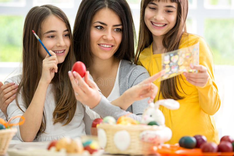 Mother and two girls making Easter decoration. In bright living room royalty free stock image
