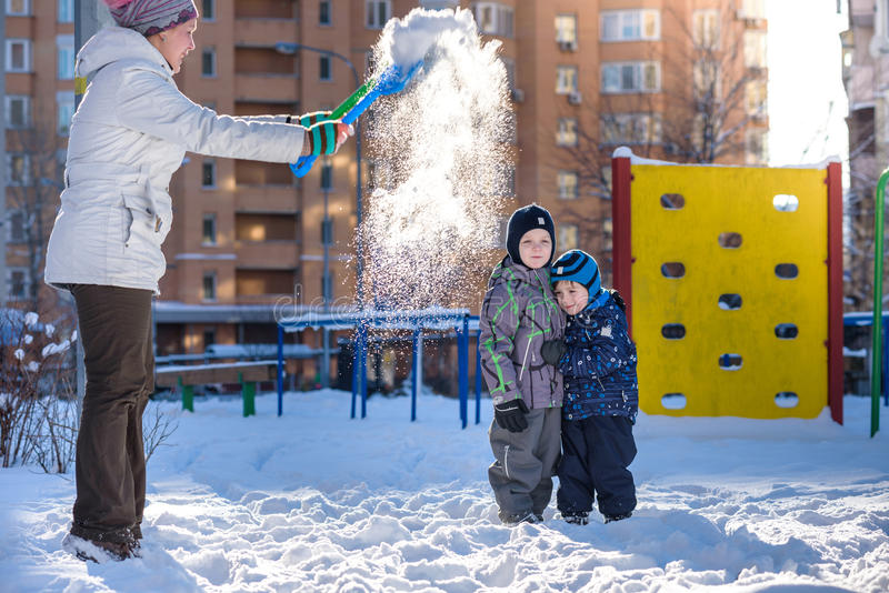 Mother and two son enjoying beautiful winter day outdoors. Kisd under snow trowing royalty free stock images