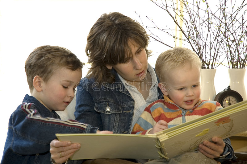 Mother and two son's reading a book stock photo