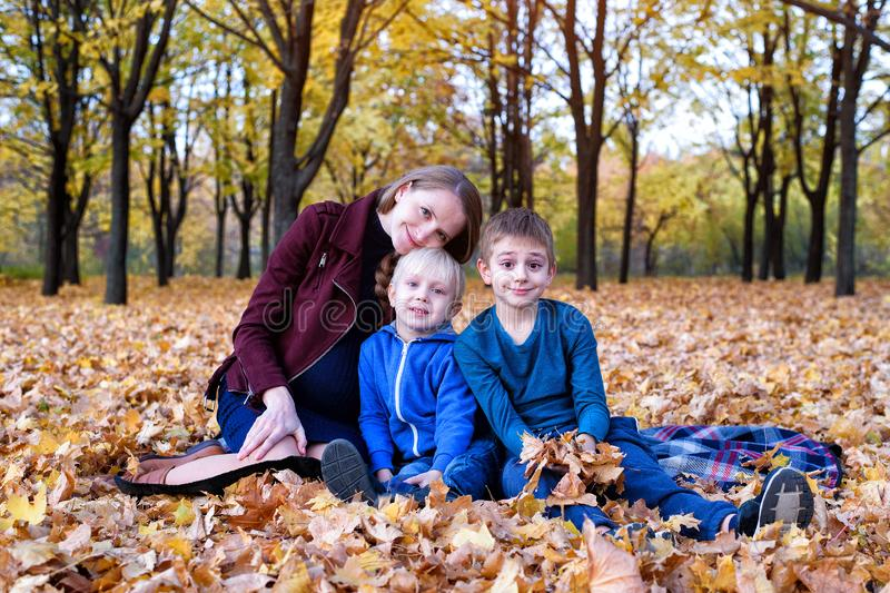Mother and two sons relax in the park. Happy family. Yellow autumn foliage, sunny day stock photos