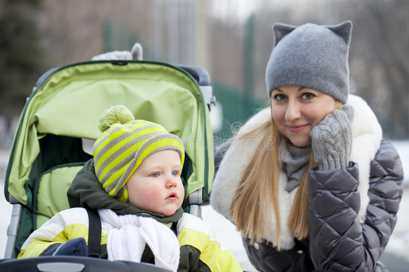 Mother with two year old son in winter park royalty free stock photography