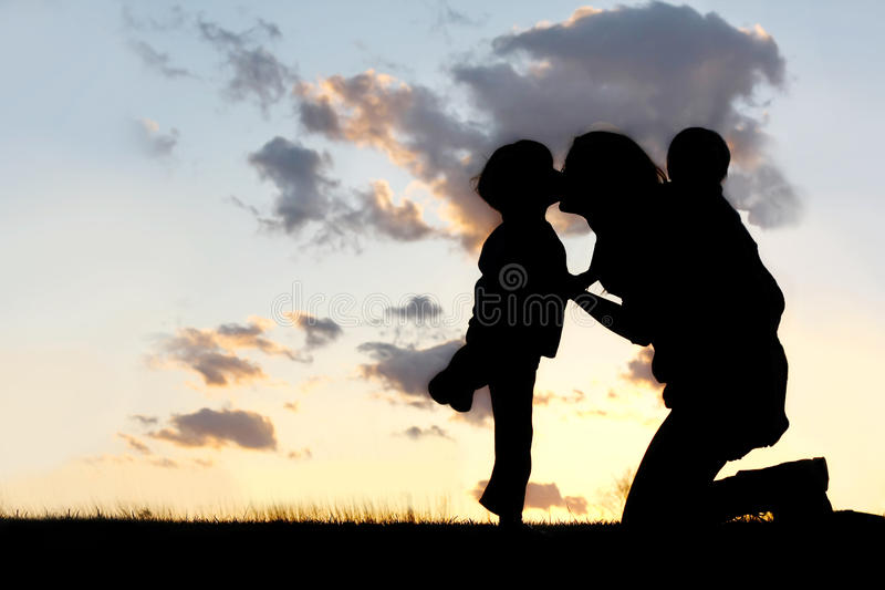 Mother and Two Young Children Hugging and Kissing stock photo