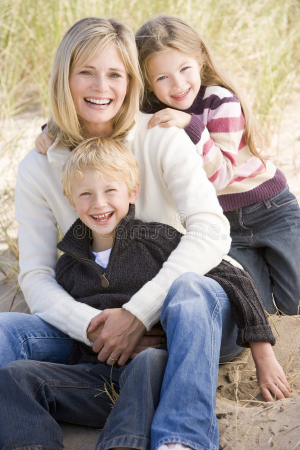 Mother and two young children sitting on beach. Smiling