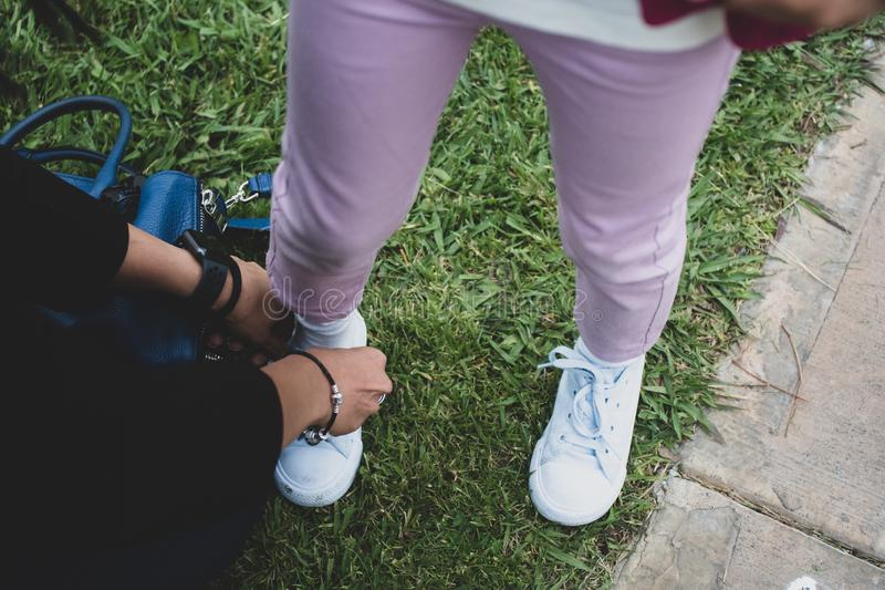 Mother tying child`s shoe laces - Mother`s Day use. stock photography