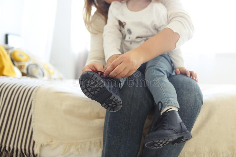 Mother is tying a shoe of a child royalty free stock images