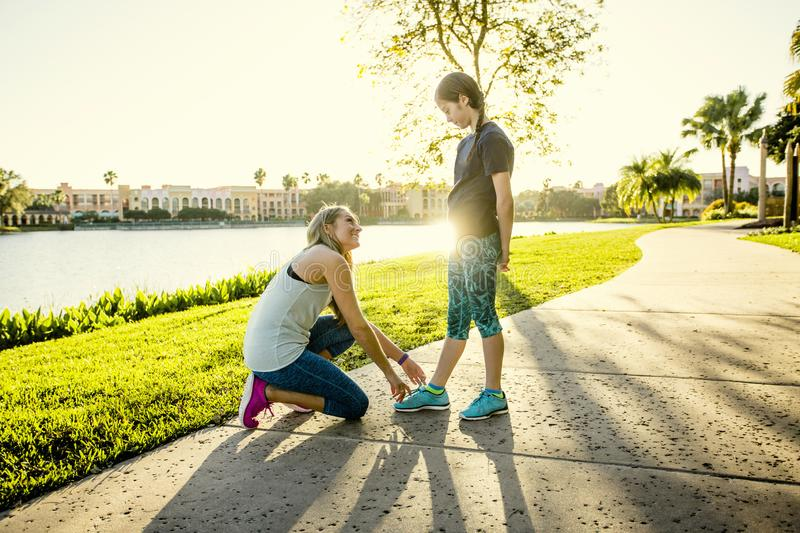 Active family going for a run together outdoors. Mother tying the shoe of her daughter before going on a jog together. Showing love and concern while sharing a stock photo
