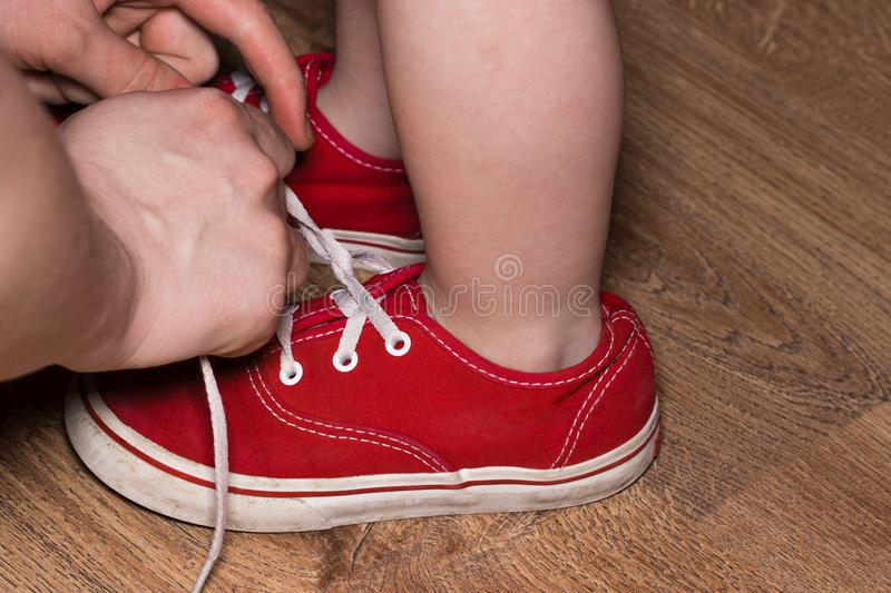 Mother tying shoe laces of his son stock images