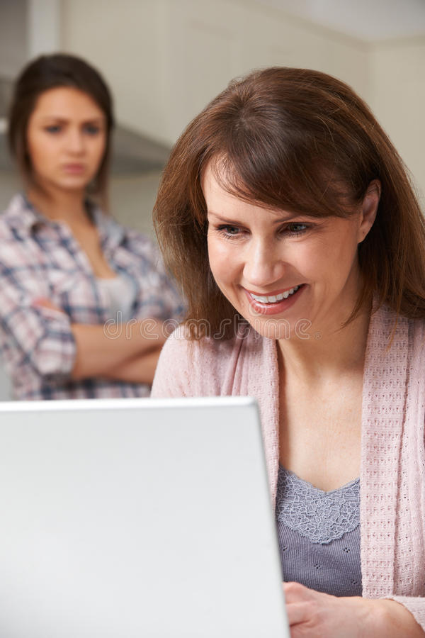 Mother Using Laptop With Frustrated Teenage Daughter In Backgrou stock photography