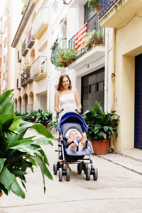 Mother walking with a baby pram royalty free stock image